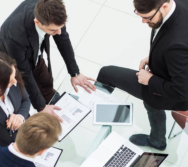 Odnoszący sukcesy zespół biznesowy omawiający przed spotkaniem grafikę marketingową