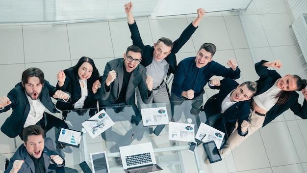 Odnoszący sukcesy zespół biznesowy siedzi przy biurku i patrzy w kamerę