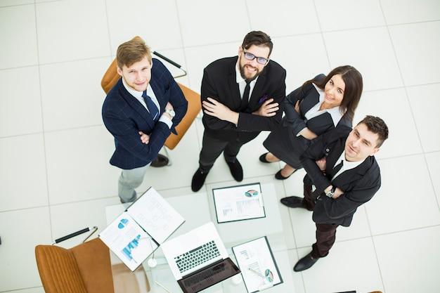 Odnoszący sukcesy zespół biznesowy stojący obok siebie w pobliżu miejsca pracy w biurze.