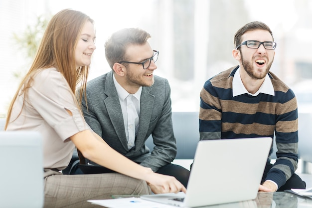 Odnoszący sukcesy zespół biznesowy z laptopem w miejscu pracy omawia pytania robocze