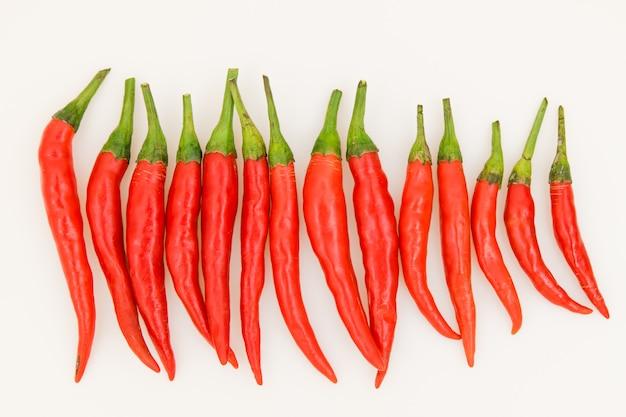 Odosobneni czerwoni chillis na bielu.