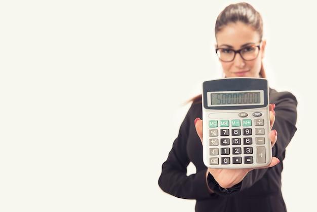 Odosobniona młoda biznesowa kobieta pokazuje kalkulator
