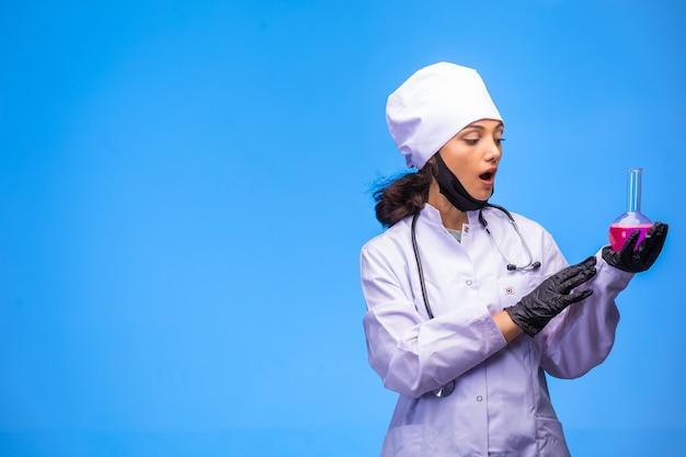Odosobniona pielęgniarka w dłoni i masce na twarz robi test i zostaje zaskoczona.