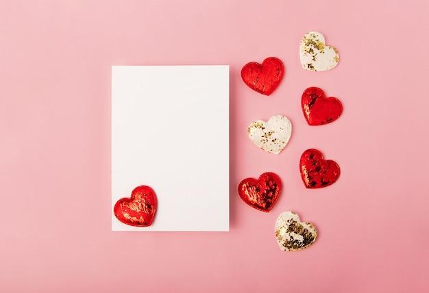 Odosobniona pusta kartka z życzeniami na różowym tle czerwone i białe serca w pobliżu