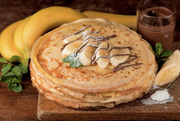 Odosobniona pustynia - stos naleśników z czekoladą i bananem na drewnianym stole