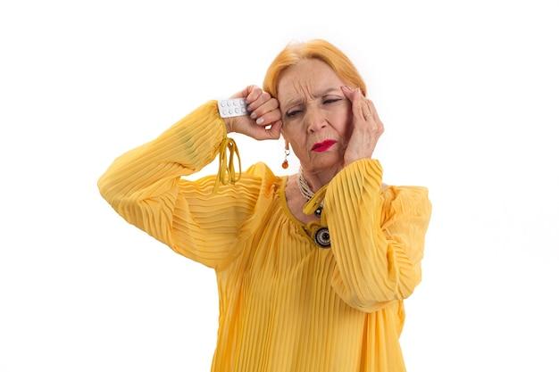 Odosobniona starsza kobieta z pigułkami zdenerwowana panią dotykającą jej głowy bierze lekarstwo na ból głowy