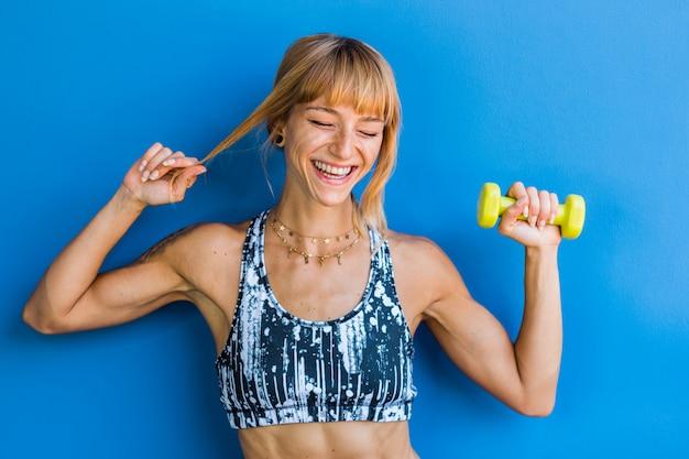 Odosobniona szczęśliwa młoda kobieta lekkoatletycznego na niebieskim tle