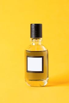 Odosobniona szklana butelka perfum leży na żółtym tle. minimalistyczny abstrakcyjny makieta. kobiety mężczyźni unisex zapach.
