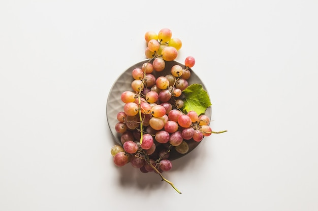 Odosobnione winogrona. czerwone winogrona w misce na białym tle