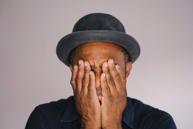 Odosobniony amerykanina afrykańskiego pochodzenia mężczyzna zakrywa jego twarz z rękami. objawy depresji i smutku.