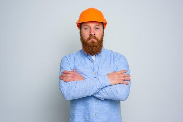 Odosobniony architekt powiernik z brodą i pomarańczowym hełmem