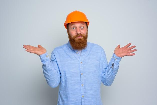 Odosobniony niepewny architekt z brodą i pomarańczowym hełmem