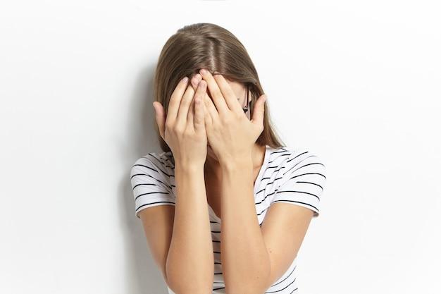 Odosobniony obraz nierozpoznawalnej młodej kobiety z rozpuszczonymi włosami, zakrywającą twarz za obiema rękami, mającą fobię społeczną, przywiązującą wagę do anonimowości. przestraszona przerażona dziewczyna w pasiastej koszulce zakrywającej twarz
