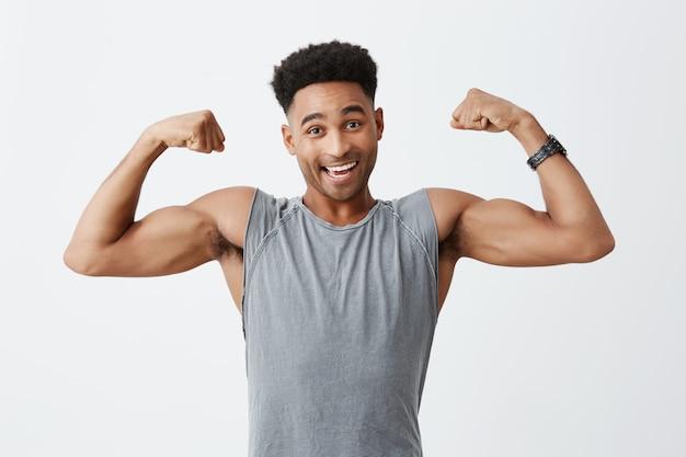 Odosobniony portret młody rozochocony atrakcyjny sportowy ciemnoskóry mężczyzna z afro fryzurą w sportowej szarej koszuli pokazującej duże mięśnie, patrząc w kamerę z radosnym i zrelaksowanym wyrazem twarzy.