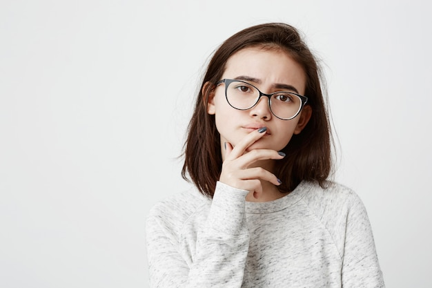Odosobniony portret stylowa nastoletnia kobieta z ciemnymi prostymi włosami dotyka jej podbródek i wargi