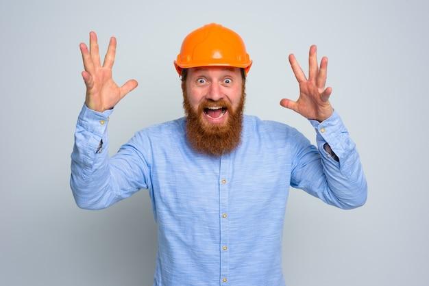 Odosobniony szczęśliwy architekt z brodą i pomarańczowym hełmem
