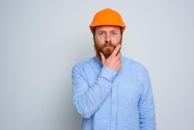 Odosobniony wątpiący architekt z brodą i pomarańczowym hełmem