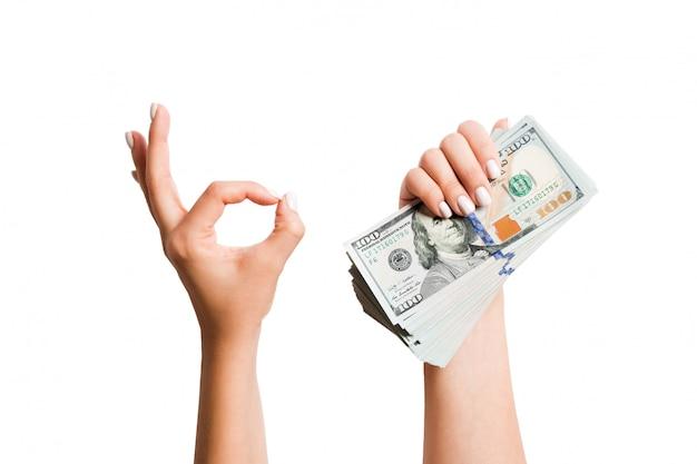Odosobniony wizerunek dolary w jednej ręce i pokazywać zadowalającego gest drugą ręką. widok z góry koncepcji biznesowej