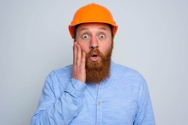 Odosobniony zdumiony architekt z brodą i pomarańczowym hełmem
