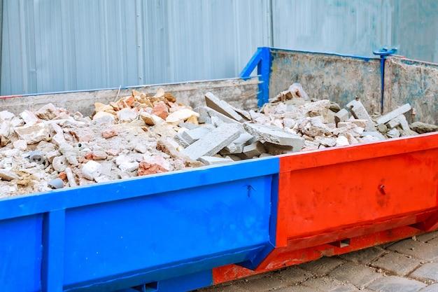 Odpady budowlane pełne na placu budowy pojemnik na odpady, cegły na śmieci