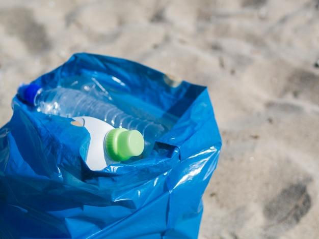 Odpady plastikowe butelki w błękitnym torba na śmiecie na piasku