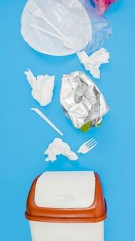 Odpady śmieci z tworzyw sztucznych w pobliżu kosza na niebieskim tle