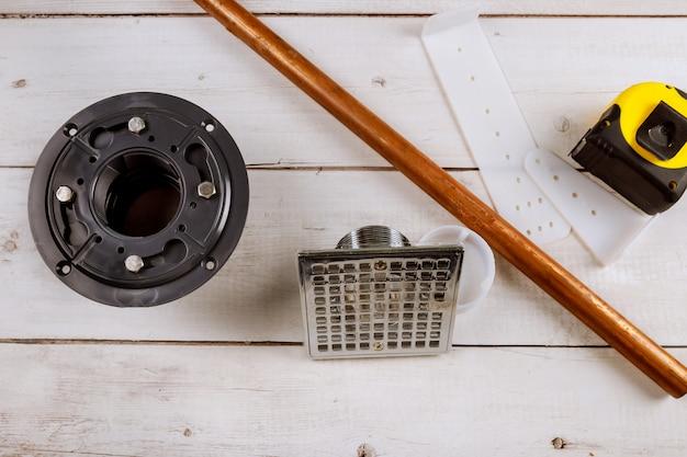 Odpływ podłogowy pod prysznicem, narzędzia hydrauliczne na miedzianych rurach