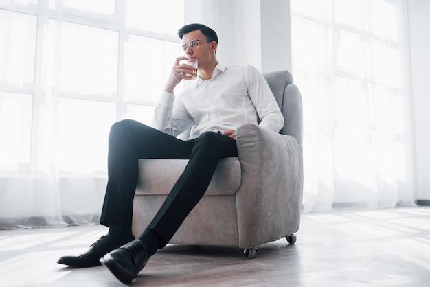 Odpocznij i uspokój. luksusowo wyglądający mężczyzna w klasycznym stroju siedzący na krześle w pokoju i trzymający szklankę z alkoholem.