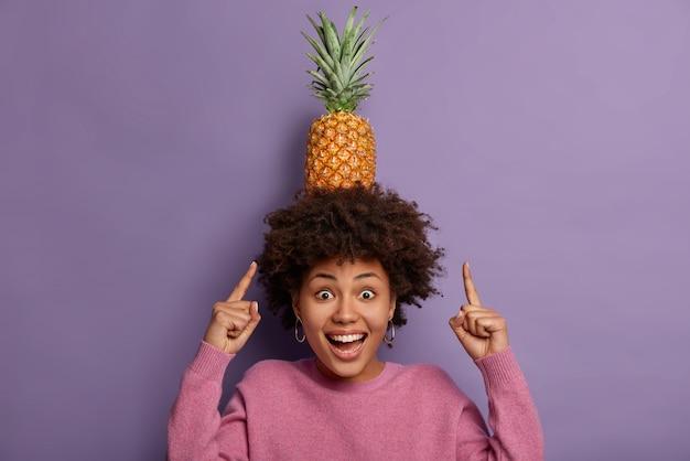 Odpocznij i zrelaksuj się. spójrz, jak mogę! radosna etniczna dziewczyna z kręconymi włosami wskazuje na dojrzałego ananasa na głowie, śmieje się pozytywnie