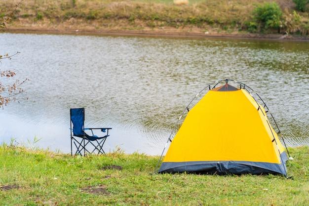 Odpocznij z namiotem w lesie nad rzeką. przyjemność natury. camping z namiotem. świeże powietrze