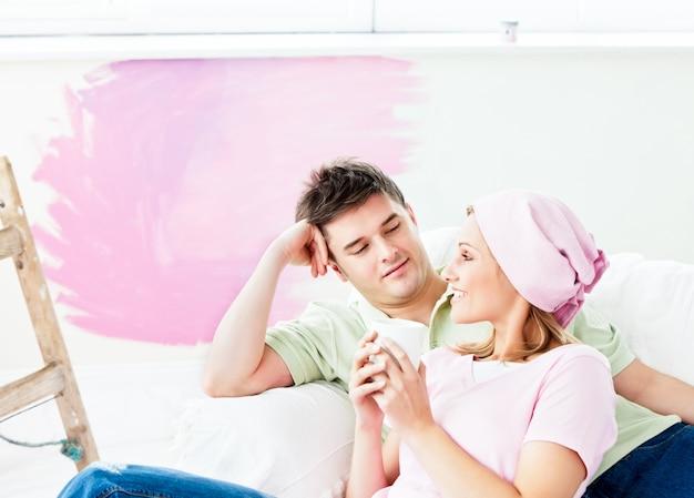 Odpoczynek kaukaski para leży na kanapie po malowaniu pokoju