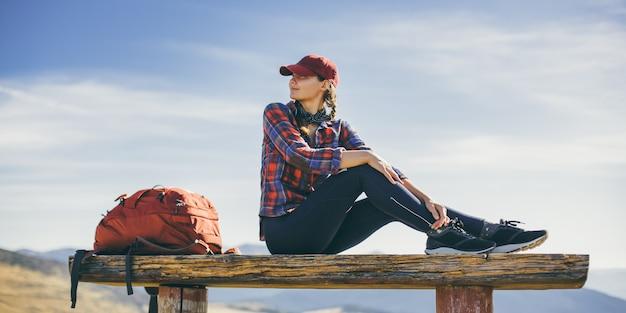 Odpoczynek kobieta turysta siedzi ciesząc się słońcem podczas wędrówki trekking piękna młoda kobieta