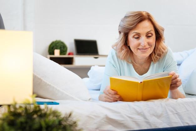Odpoczynek na łóżku. pozytywna uśmiechnięta kobieta leżąca na łóżku i czytająca książkę w twardej oprawie podczas spokojnego poranka