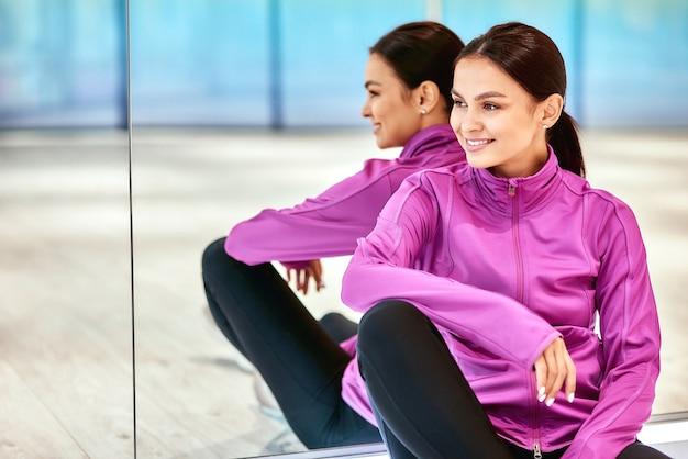 Odpoczynek po treningu. młoda piękna kobieta fitness w odzieży sportowej, odwracając wzrok i uśmiechając się, siedząc na podłodze w studio, opierając się o ścianę lustrzaną. sport, wellness i zdrowy styl życia
