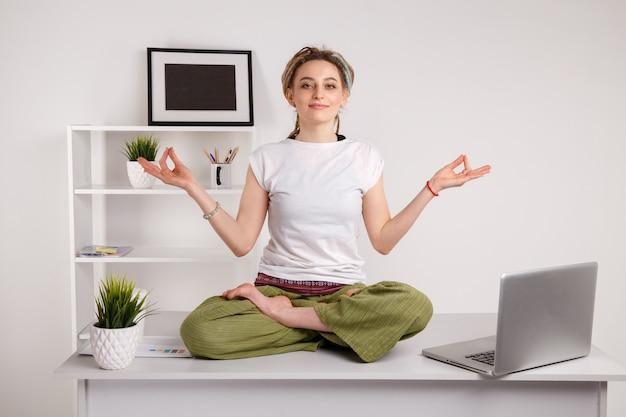 Odpoczynek w biurze. joga w pracy. pisanie na laptopie i robienie pozy lotosu.