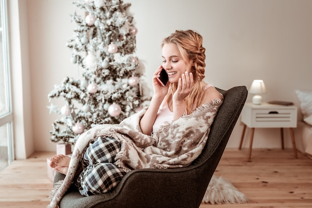 Odpoczynek w fotelu. zadowolona jasnowłosa kobieta przyjemnie rozmawia na smartfonie podczas świąt bożego narodzenia w domu