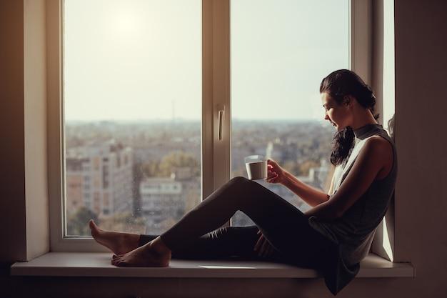 Odpoczywająca i myśląca kobieta. spokojna dziewczyna z filiżanką herbaty lub kawy siedzi na parapecie przy