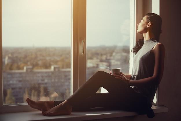 Odpoczywająca i myśląca kobieta z zamkniętymi oczami. spokojna dziewczyna z filiżanką herbaty lub kawy, siedząc na