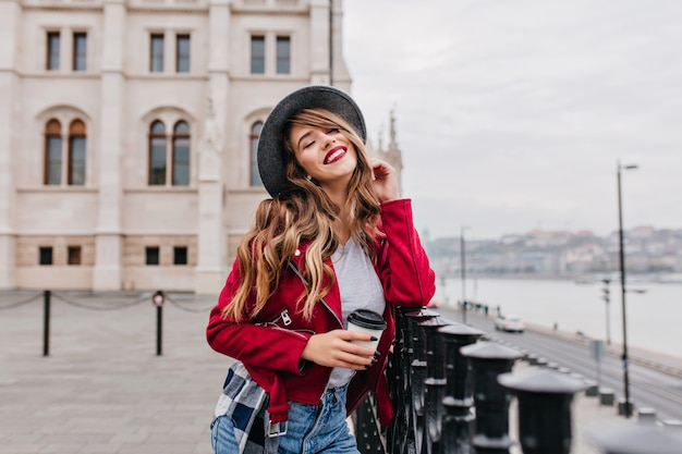 Odpoczywająca kobieta w modnym kapeluszu pozuje z zamkniętymi oczami na rozmycie ściany ulicy i pije latte