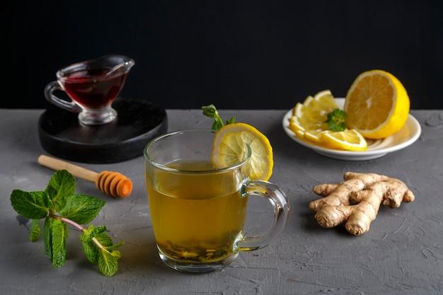 Odporny napój imbirowy z miodem mięty i cytryną w szklanej filiżance w pobliżu składników na betonowym tle.