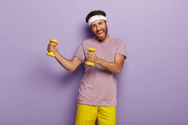 Odporny pozytywny człowiek ma trening z dwoma żółtymi ciężarkami, doskonałą kondycję fizyczną