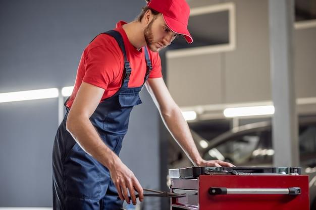 Odpowiednia opcja. poważnie zainteresowany młody mężczyzna w czerwonej koszulce i niebieskim kombinezonie wybiera odpowiedni element w pobliżu skrzynki z narzędziami