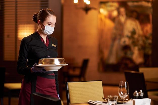 Odpowiedzialna kobieta w stołach z maskami i serwująca jedzenie