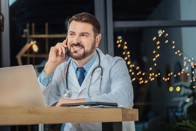 Odpowiedzialna praca. inteligentny, profesjonalny lekarz główny siedzi w swoim gabinecie i rozmawia przez telefon podczas pracy w godzinach nadliczbowych