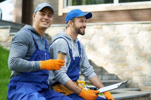 Odpowiedzialni kontrahenci. szczęśliwi młodzi robotnicy w mundurach robiący sobie przerwę, siedzący na zewnątrz przy kawie i trzymający papiery podczas pracy nad projektem budowlanym