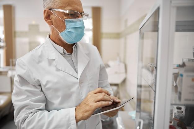 Odpowiedzialny pracownik służby zdrowia noszący maskę i trzymający tablet podczas sprawdzania sprzętu medycznego w szafce