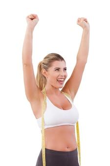 Odpracowano nadwagę. szczęśliwa młoda kobieta z miarką na ramionach, podnoszącą ręce do góry i uśmiechającą się, stojąc na białym tle