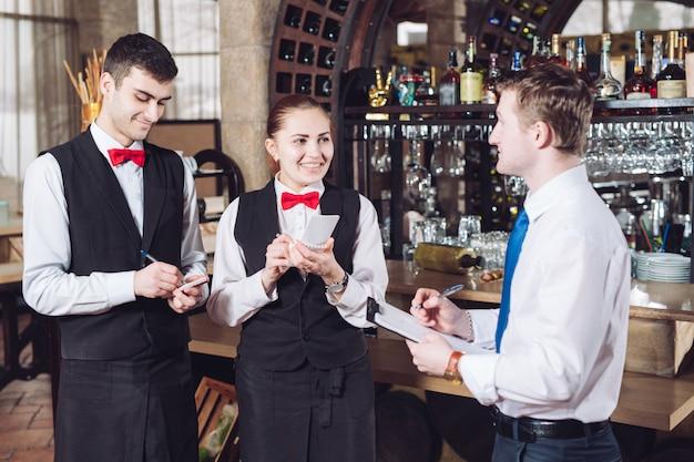 Odprawa menedżera z kelnerami. kierownik restauracji i jego pracownicy.
