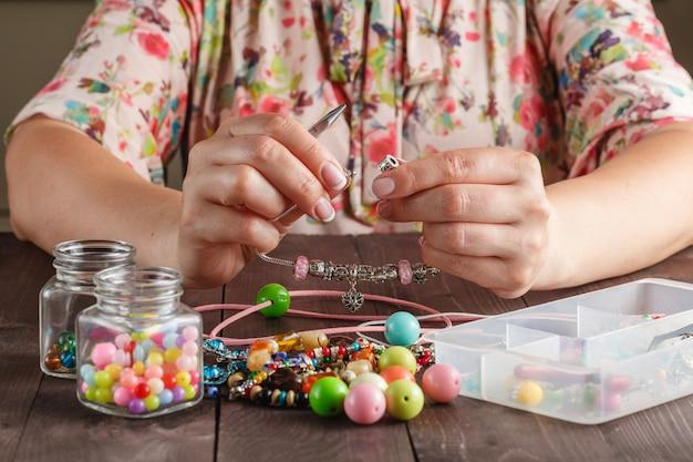 Odpręż hobby. kobieta produkuje koraliki rzemieślnicze