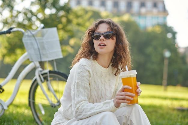 Odprężający. dziewczyna w bieli siedzi na trawie w parku i wygląda na zrelaksowaną